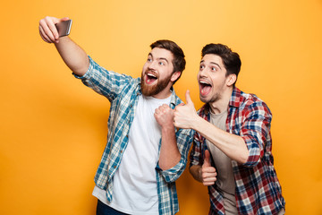 Portrait of a two excited young men taking a selfie