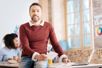 I am professional. Attractive cheerful bearded man holding sheets of paper and sitting on the table while his colleagues working in the background