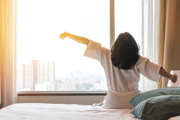 Simple city lifestyle happy woman waking up in the morning taking some rest relaxing in luxury comfy city hotel room