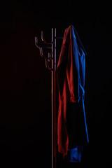 coat hanging on coat rack under toned light isolated on black