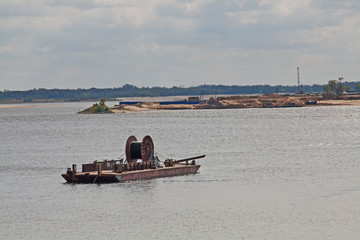 Cable laying on the bottom of the river using a surface platform with a cable drum