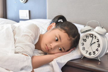 School kid suffering insomnia (sleeping disorder), mental health illness concept with Asian girl child cannot sleep on bed at night in bedroom