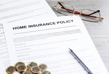Home insurance policy. Glasses, pen and home insurance policy. Business background concept. Mortgage loading real estate property with house and money concept