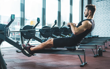 Young sportsman doing exercise on rowing machine in sports center