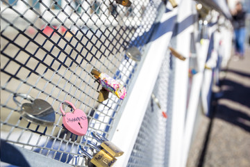 Love locks hanging on a from white metal footbridge, Helsinki, Finland. Shallow depth of field and bokeh.