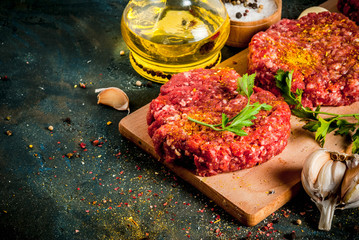Raw burger cutlets with salt, pepper, oil, herbs and spice, on dark table, copy space