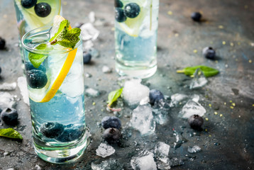 Summer refreshment drinks, Blueberry Lemonade or mojito cocktail with lemon, fresh blueberries and mint, sdark blue stone background copy space