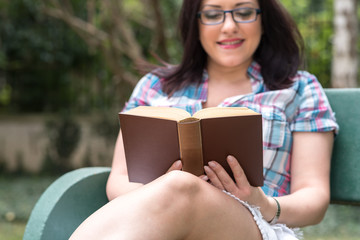 Portrait of beautiful young woman reading a book on a bench in park