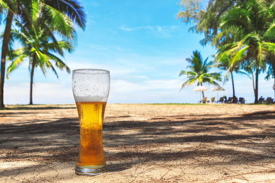 Misted glass of cold beer on the sand at the background of green palm trees, blue sky and sea coast. Tropical island. Heavenly delight.