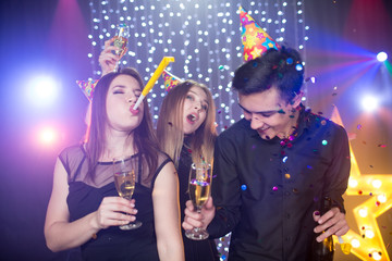 Three young men and two women in hoods and with glass champagne celebrate a birthday have fun in a nightclub