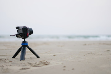 Small camera on stand Take a photo of the sea in the summer vacation concept