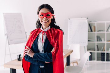 attractive super businesswoman in cape and mask standing with crossed arms in office