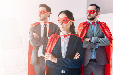super businesspeople in masks and capes looking away with crossed arms in office