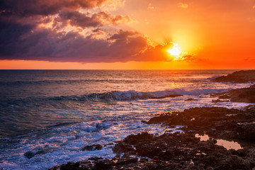 Fantastic stunning colorful sunset by the sea, waves and sunlight