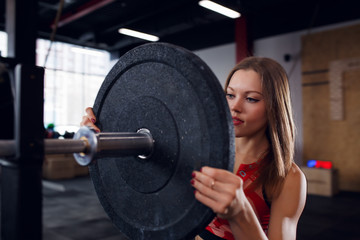 Image of athlete woman in sports clothes with barbell