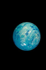 Blue glass sphere on a black background, similar to the Earth in space