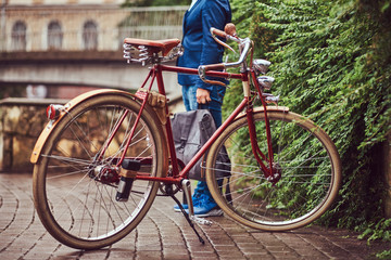 Male dressed in casual clothes, standing near a retro bicycle in a park.