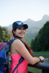 Photo of tourist girl with backpack against backdrop of picturesque mountains