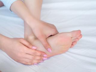 Closeup woman hands doing foot massage. Color picture