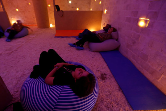 A group sits in the salt cave during a meditation session in Amman