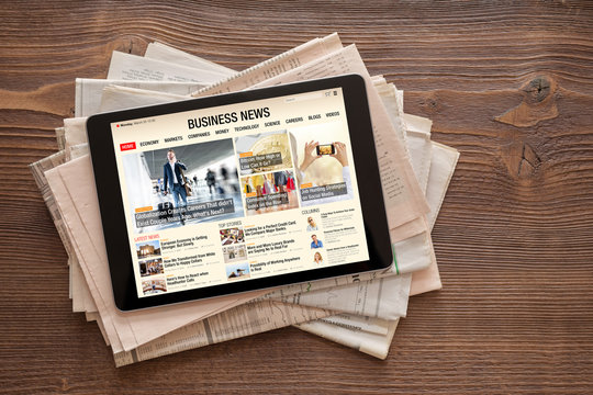 Tablet with business news website on stack of newspapers. All contents are made up.