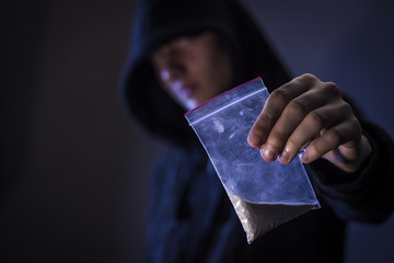 Mans hand holds plastic packet with cocaine powder
