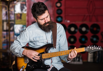 Musician with beard play electric guitar musical instrument.