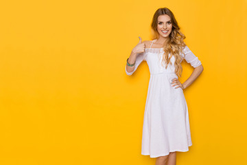 Smiling Elegant Woman In White Dress Gives Thumb Up