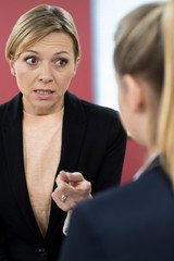 Aggressive Businesswoman Shouting At Female Colleague
