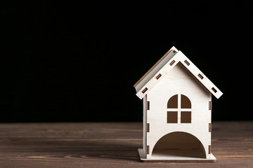 Wooden decorative toy house standing on wooden surface on black background.