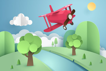 Paper art of pink plane flying above forest and river