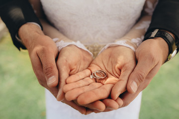 Bride and groom holding wedding rings