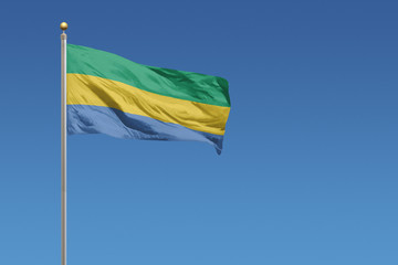 Flag of Gabon in front of a clear blue sky