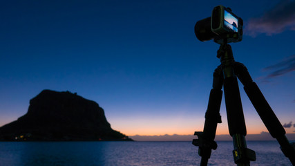 Camera and Monemvasia island at sunrise