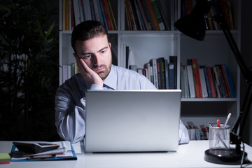 Businessman working and watching laptop display at night