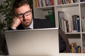 Tired and worried businessman working in the office at night