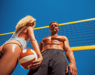 Sports couple. A handsome muscular tanned male and sexy tanned blonde girl, standing on a volleyball ground.