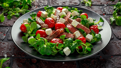 Juicy Beef Sirloin Steak Salad with roasted tomatoes, feta cheese and green vegetables in a black plate. healthy food