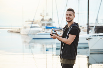 Attractive boyfriend focused on his hobby during walk with girlfriend. Portrait of handsome guy standing in harbour near yachts, holding camera, looking aside while searching for great shot.
