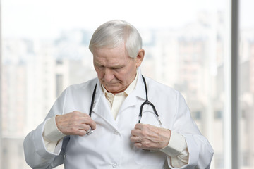 Old pharmacist with stethoscope. Put on medical equipment. Bright blurred windows background.