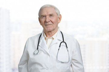 Portrait of smiling old caucasian doctor in lab coat. Senior physician in stethoscope in bright background.