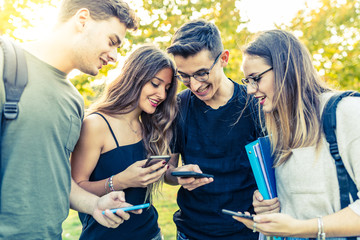 Teen group of friends with smartphones at park