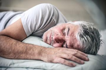 Sleepy senior man in bed. Wall mural