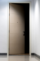 The mysteriously open door to the dark room. Illuminated corridor of a residential house with open door to the apartment without light.
