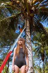 attractive young woman with long hair posing near palm tree with surfboard