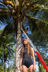 attractive tanned girl with long hair posing near palm tree with red surfboard