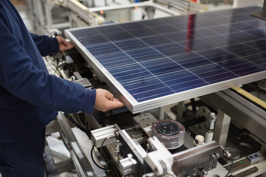 production of solar panels, man working in factory.