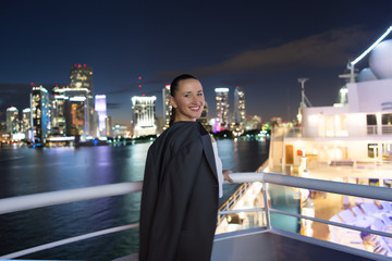 Business woman smile in suit jacket in miami, usa. Sensual woman on ship board on night skyline. Fashion, beauty, look. Travelling for business. Wanderlust, adventure, discovery, journey