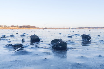 Black rocks in the ice on a frozen lake