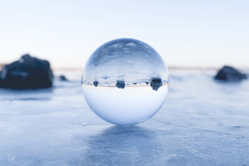 Glass orb balancing on ice on a frozen lake